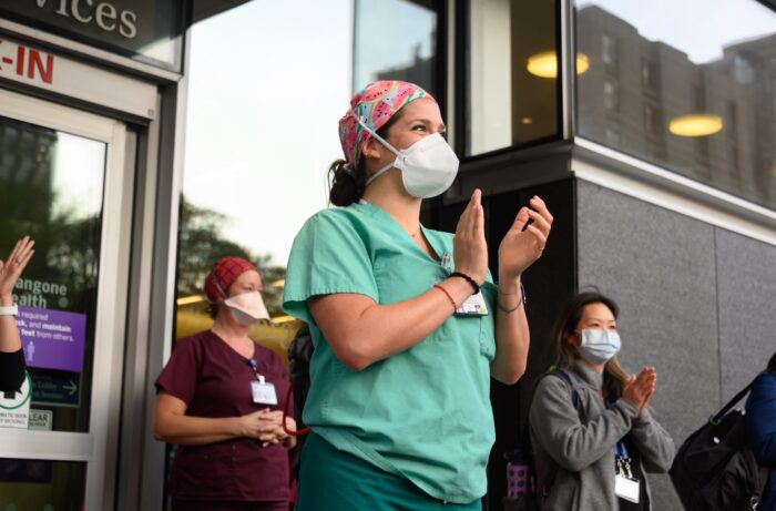 NEW YORK, NEW YORK - MAY 19: Medical workers wearing protective masks stand outside NYU Langone Health hospital as people applaud to show their gratitude to medical staff and essential workers during the coronavirus pandemic on May 19, 2020 in New York City. COVID-19 has spread to most countries around the world, claiming over 324,000 lives with over 4.9 million infections reported. (Photo by Noam Galai/Getty Images)