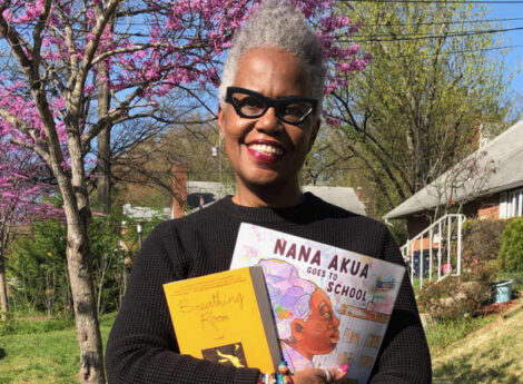 """Tricia Elam Walker with her book """"Nana Akua Goes to School"""" outside in Maryland. Photo by Chuck Walker."""